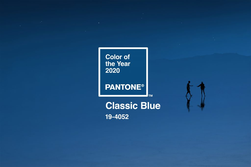 """Color of the Year 2020, Pantone, Classic Blue 19-4052"" Two silhouetted individuals reaching towards each other in front of a rich, dusk blue."
